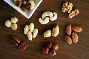 variety-of-brown-nuts-on-brown-wooden-panel-high-angle-photo-1295572