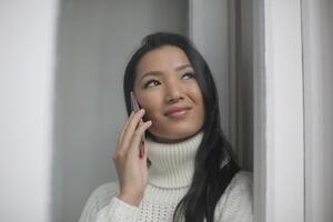 woman-in-white-knit-sweater-speaking-on-mobile-phone-3973188